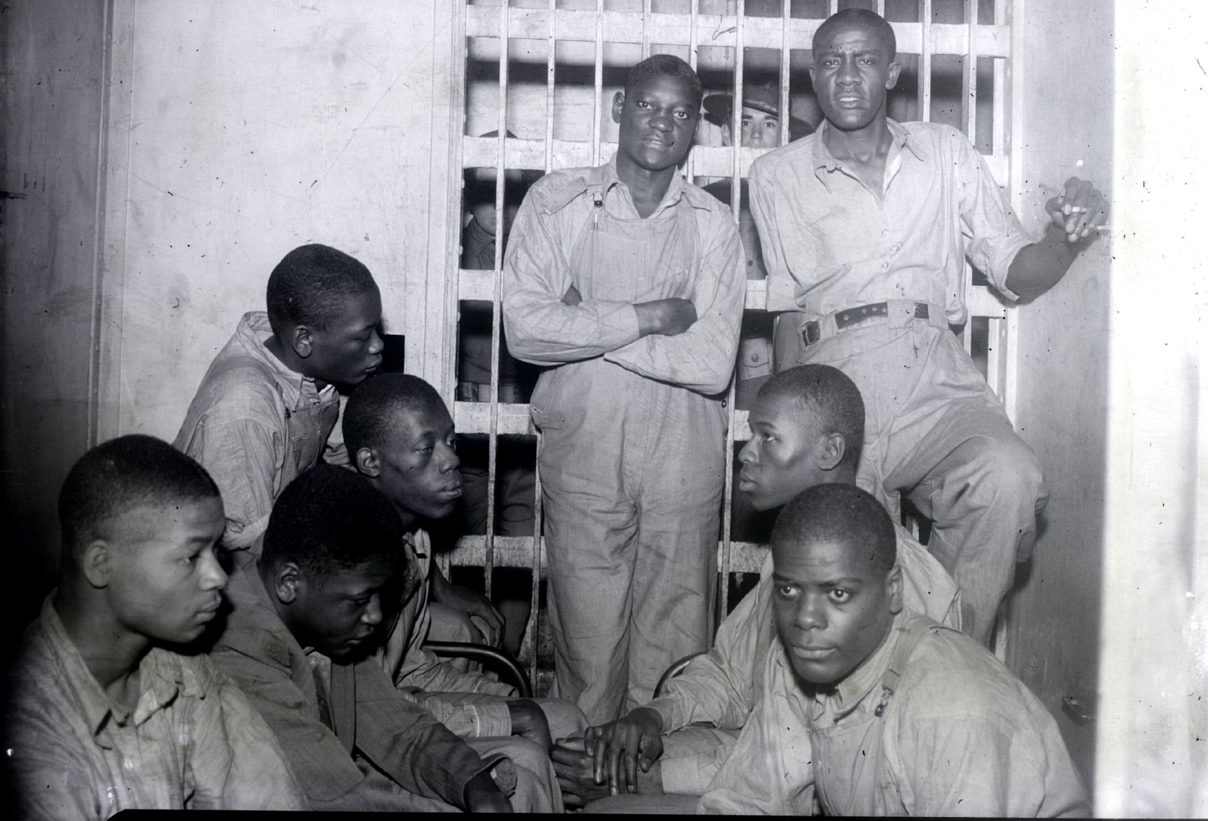 8 Scottsboro Boys stand in a jail cell